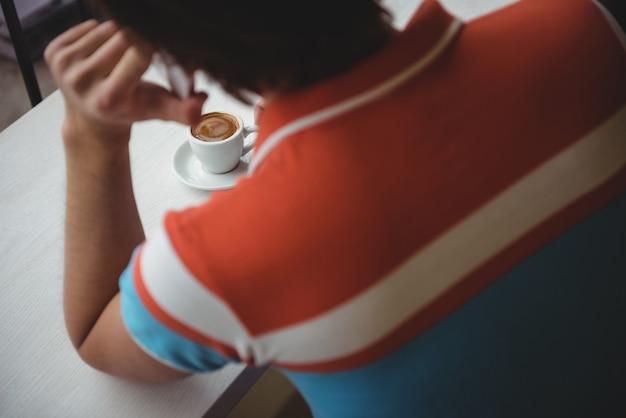 Mężczyzna rozmawia przez telefon komórkowy z filiżanką kawy na stole