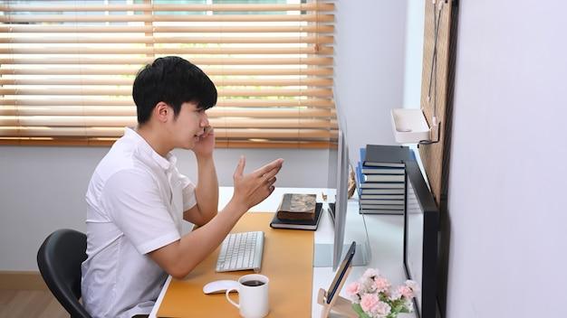 Mężczyzna rozmawia przez telefon komórkowy ze swoim partnerem biznesowym, siedząc w wygodnym biurze.