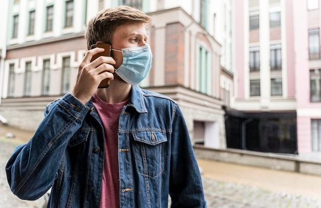 Mężczyzna rozmawia przez telefon mając na sobie maskę medyczną