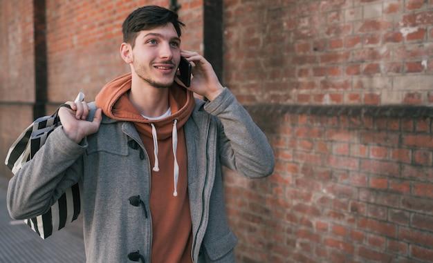 Mężczyzna rozmawia przez telefon na zewnątrz.