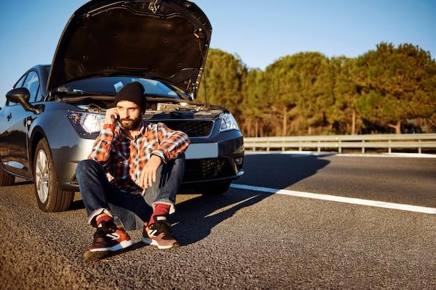 Mężczyzna rozmawia przez telefon obok samochodu