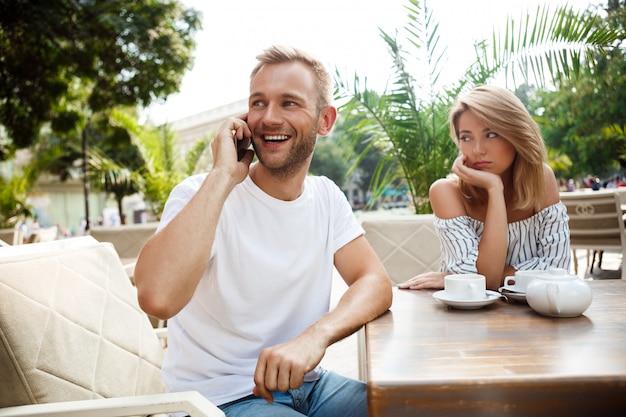 Mężczyzna rozmawia przez telefon, podczas gdy jego dziewczyna się nudzi.