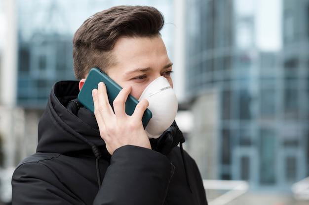 Mężczyzna rozmawia przez telefon podczas noszenia maski medyczne