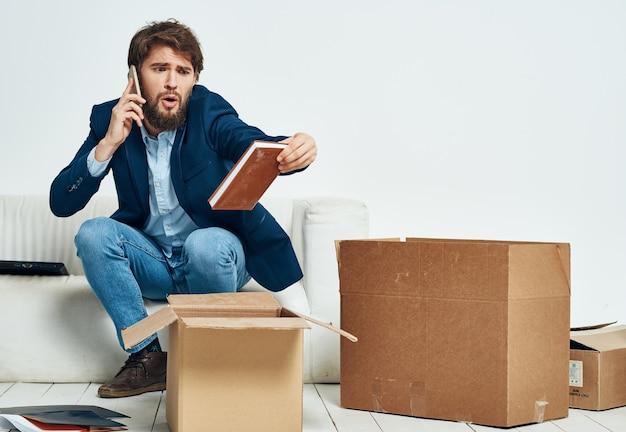 Mężczyzna rozmawia przez telefon siedzi na pudełkach na kanapie z rzeczami w ruchu rozpakowywania