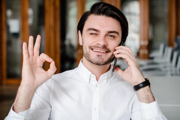 Mężczyzna rozmawia przez telefon, uśmiecha się i pokazuje ok gest
