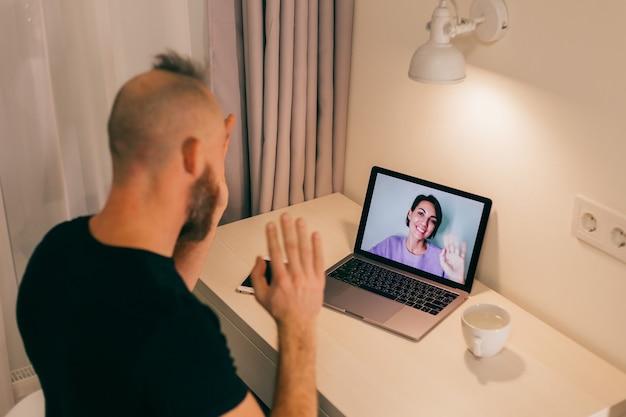 Mężczyzna rozmawia przez telefon w domu, dzwoniąc do swojej przyjaciółki, żony, dziewczyny z laptopa w sypialni.