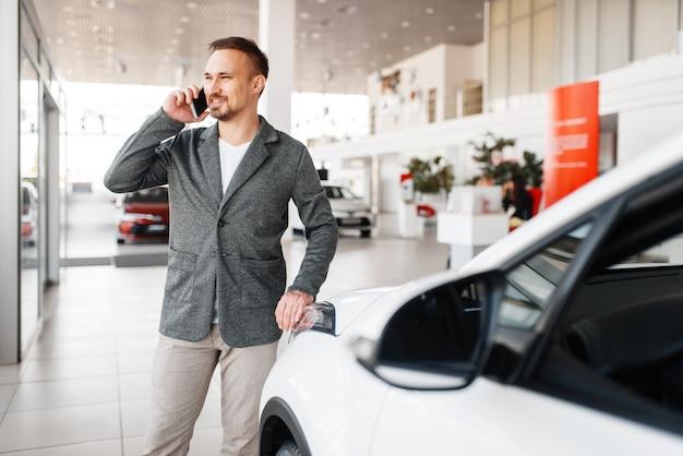 Mężczyzna rozmawia przez telefon w pobliżu nowego samochodu w salonie.