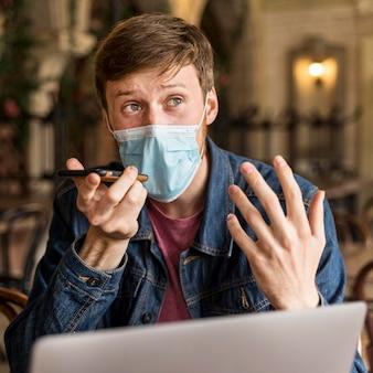 Mężczyzna rozmawia przez telefon w pomieszczeniu, mając na sobie maskę medyczną