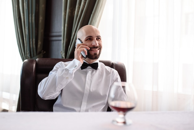 Mężczyzna rozmawia przez telefon w restauracji.