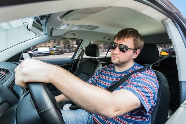 Mężczyzna rozmawia przez telefon w samochodzie