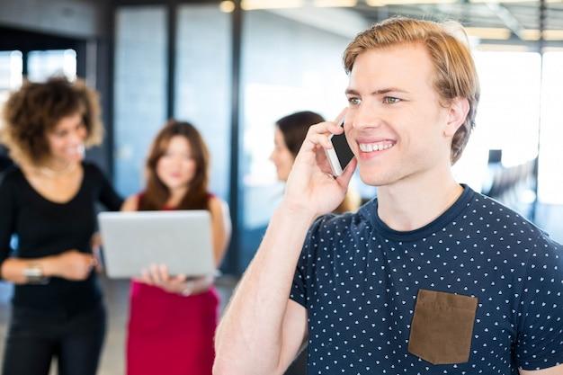 Mężczyzna rozmawia przez telefon z koleżanki stojącej obok w biurze
