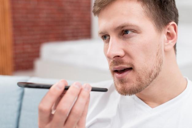 Mężczyzna rozmawia z kimś z włączonym głośnikiem