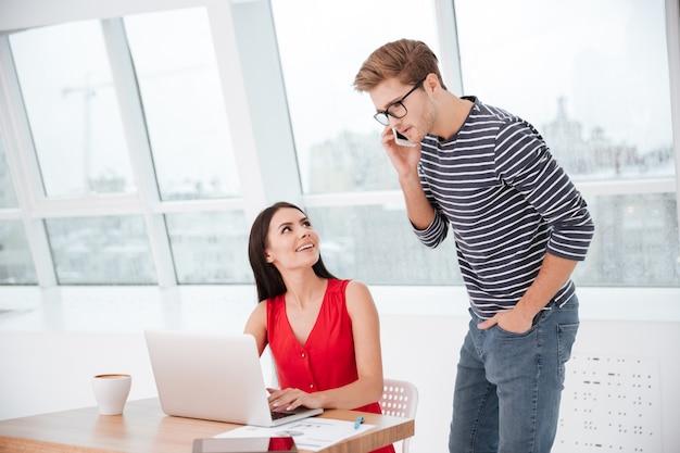 Mężczyzna rozmawiający przez telefon i stojący obok kobiety przy stole w biurze przy oknie