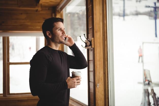 Mężczyzna rozmawiający przez telefon przed oknem