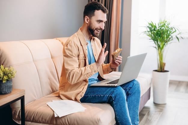 Mężczyzna rozmawiający przez wideokonferencję, je kanapkę i siedzi na kanapie w swoim przytulnym salonie