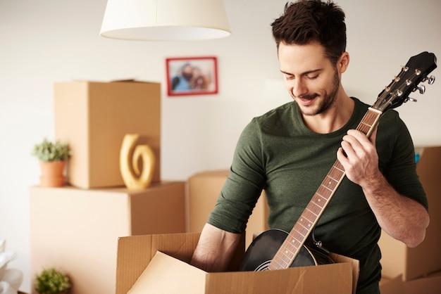 Mężczyzna rozpakowujący gitarę z kartonu