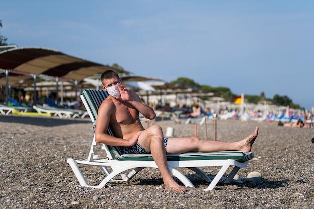 Mężczyzna rozpryskuje się samotnie na otwartym morzu w masce podczas epidemii 19 wirusa grypy