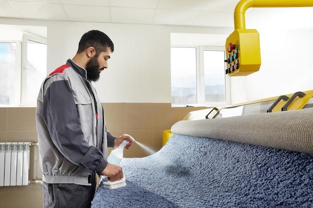 Mężczyzna rozpyla detergent na szarym dywanie w celu usunięcia plam w profesjonalnych usługach sprzątania