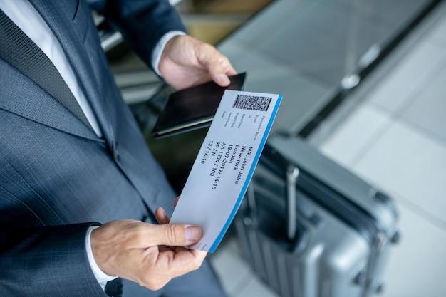 Mężczyzna rozważa bilet lotniczy na lotnisku?