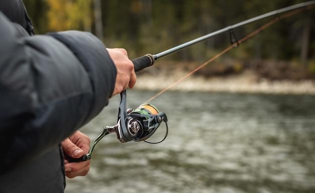 Mężczyzna rybak łowi ryby w spokojnym miejscu nad rzeką w jesiennym lesie. zbliżenie