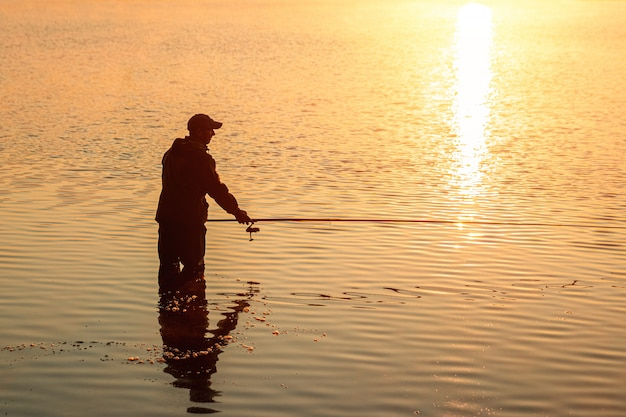 Mężczyzna rybak o świcie nad jeziorem łapie wędkę wakacje hobby wakacje