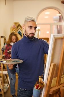 Mężczyzna rysuje obraz, a za nim stoi kobieta