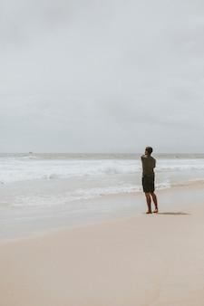 Mężczyzna rzuca kamień do morza