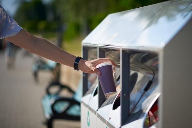 Mężczyzna rzuca papierową filiżankę kawy w koszu na odpady
