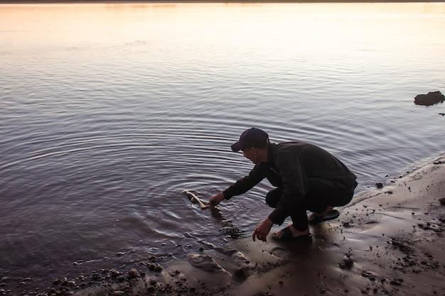 Mężczyzna rzuca rybę z powrotem do wody na brzegu rzeki.