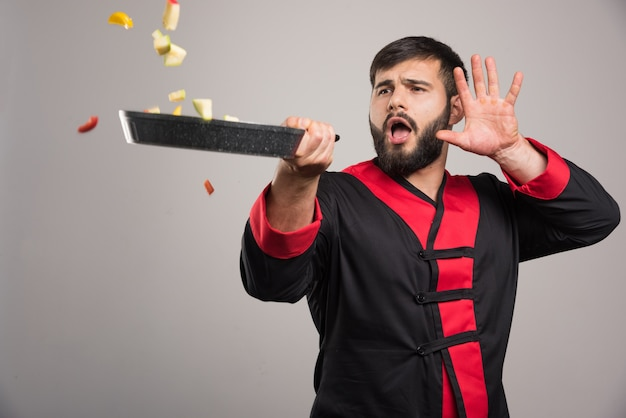 Mężczyzna rzuca warzywa z patelni.
