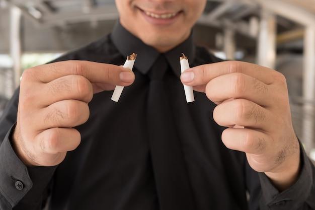 Mężczyzna rzucił palenie, łamanie papierosów, koncepcja zdrowego stylu życia