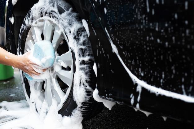 Mężczyzna sam myje koła swojego samochodu
