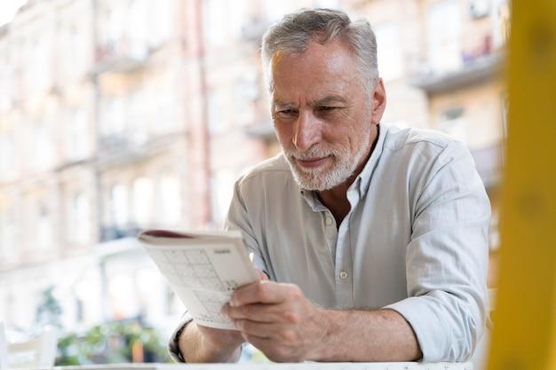 Mężczyzna samotnie grający w sudoku na papierze