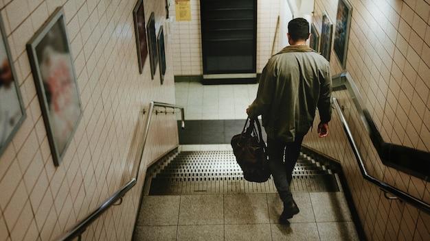 Mężczyzna schodzący ze schodów w kierunku stacji metra