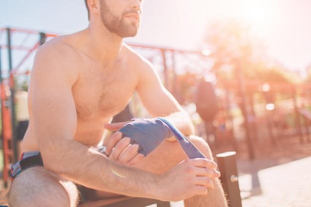 Mężczyzna ściąga bandaże bokserskie siedząc w kącie. gej w odzieży sportowej przygotowuje się do sparingu. pierścień bokserski pod gołym niebem.