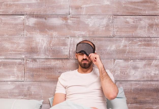 Mężczyzna ściąga maskę snu przed pójściem spać w wygodnym łóżku.