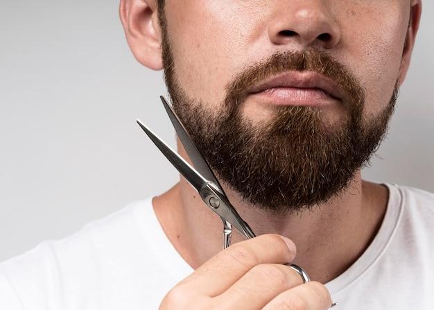 Mężczyzna ścinając brodę z bliska