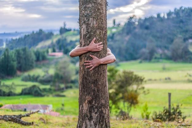 Mężczyzna ściska drzewa