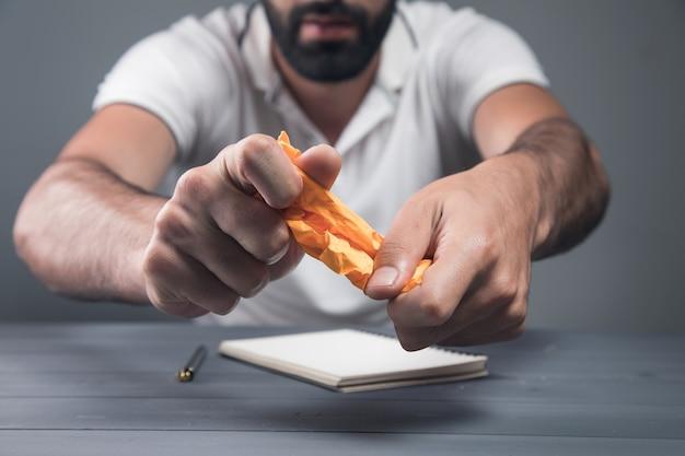 Mężczyzna ściska papier. pomysł na koncepcję
