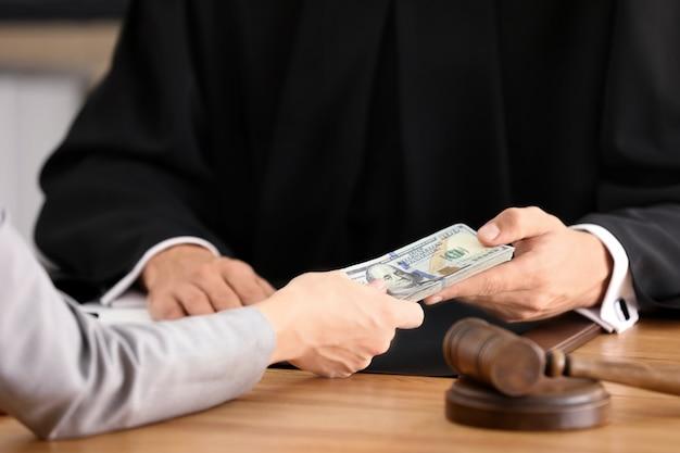 Mężczyzna sędzia bierze łapówkę od kobiety, zbliżenie