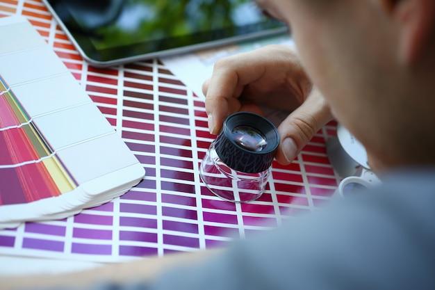Mężczyzna serwisant trzymać w ręku szkło powiększające, co test koloru