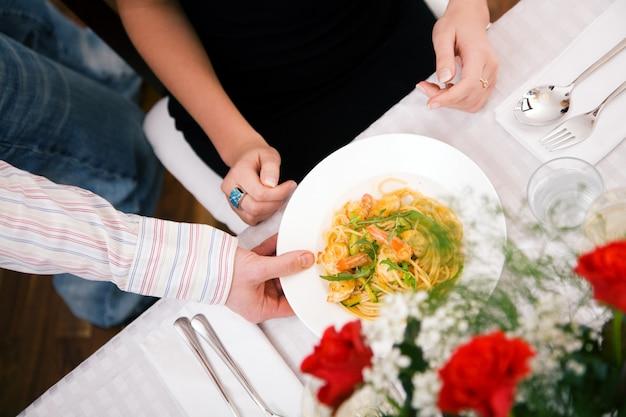 Mężczyzna serwujący obiad do swojej żony