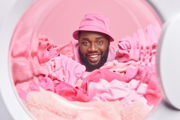Mężczyzna sfotografowany z wnętrza pralki ładuje pralkę z brudnym praniem nosi panama