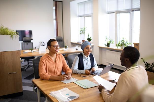 Mężczyzna siada do rozmowy kwalifikacyjnej przy biurku ze swoimi pracodawcami