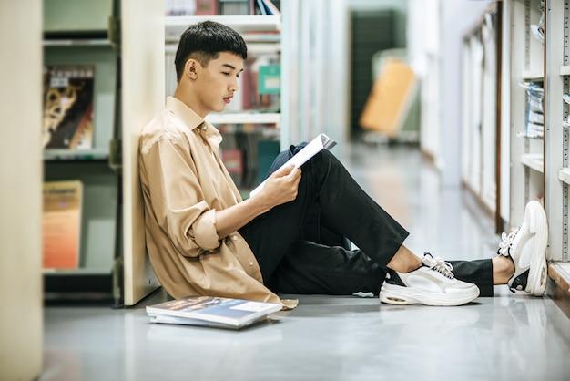 Mężczyzna siedzący i czytający książkę w bibliotece.