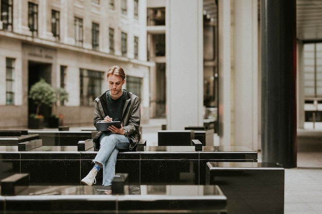 Mężczyzna siedzący i korzystający z cyfrowego tabletu w mieście