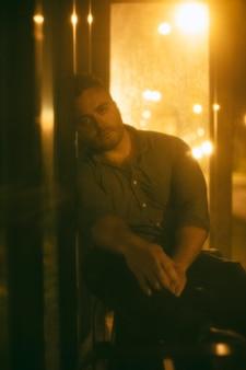 Mężczyzna siedzący na dworcu autobusowym w nocy w mieście