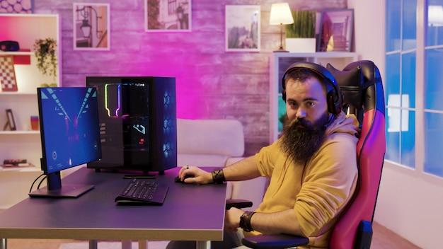 Mężczyzna siedzący na fotelu do gier i grający w gry wideo w swoim pokoju z kolorowymi neonami w słuchawkach.