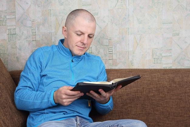 Mężczyzna siedzący na kanapie i czytający księgę biblii