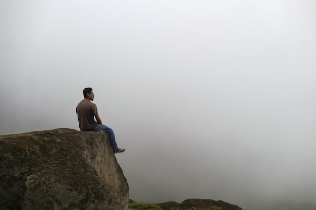 Mężczyzna siedzący na klifie w dolinie patrzący na mgłę